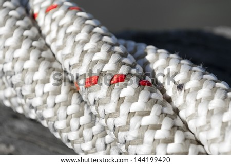 The black and white texture of a close-up of twisted ship cord with red accents only