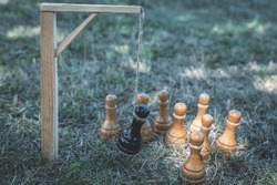The black chess pawn is executed and hangs on the gallows in the noose and around the white pieces. Metaphor, the concept of reprisal, persecution, repression, execution of the enemy, betrayal
