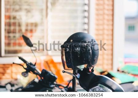 The black helmet hangs on the rearview mirror of the motorcycle #1066383254