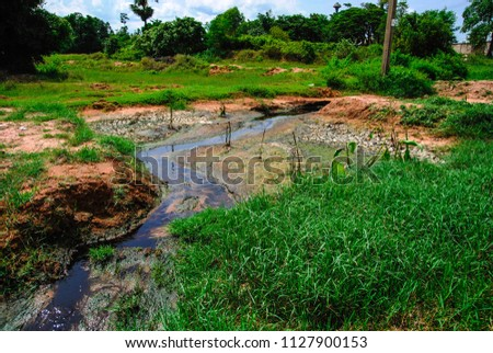 The black industrial waste was dumped into the creek. Pollution affects and affects the environment in the communities and farms of neighboring farmers.
