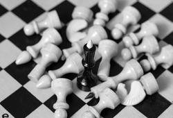 The black king stands on the chessboard, white pieces lie around him