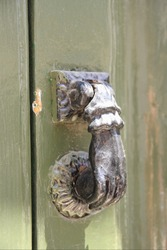 The black metal knocker on the old dilapidated wooden door, Portugal