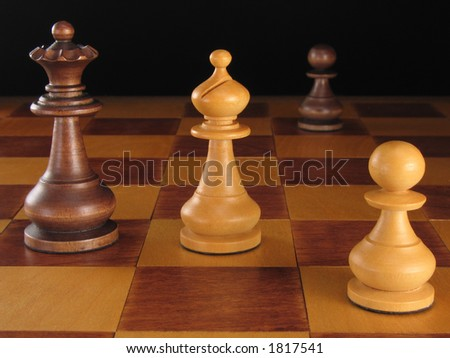 The black queen and white bishop of a wooden chess set in a standoff.