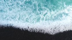 The black sand beach in Dunedin, New Zealand.  Beach on aerial drone top view with ocean waves reaching shore, top view aerial photo from flying drone of an amazingly beautiful sea landscape.