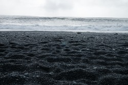 The Black sand beach of Reynisfjara, Vik and the mount Reynisfjall from the Dyrholaey promontory and Volcanic rock in the southern coast of Iceland with eroded stone arch visible in distance