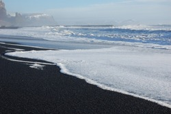 the black seashore of the boundless lava beach of Vik in Iceland with the white foam of the ocean waves in a beautiful sunny day in winter time