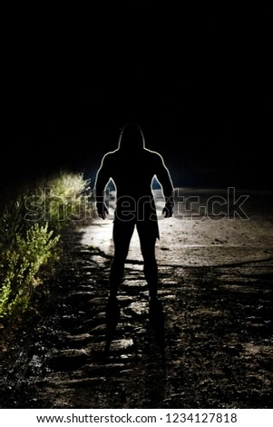 The black silhouette of a physically strong man lit by car headlights light broken roads and dangerous companion