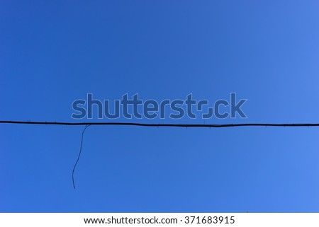 The black wire from the ragged end on plastic mounts against the blue sky #371683915