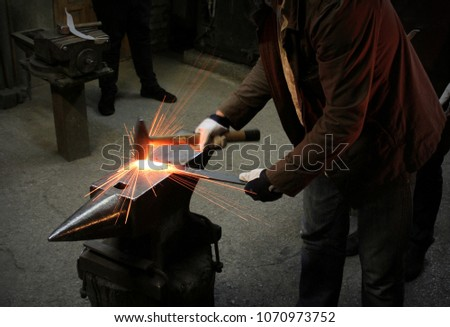 The blacksmith manually forging the molten metal on the anvil in smithy with spark fireworks. Spark. Dark background. #1070973752
