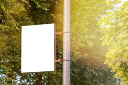 The blank advertising banner suspended on the street lamp pole with the sunlight from the tree background.