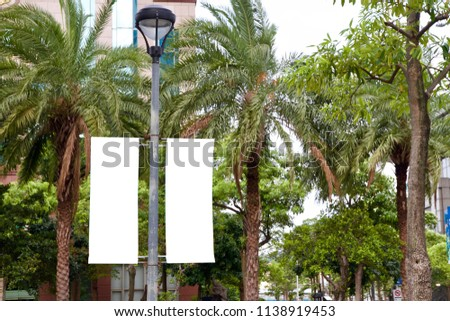 The blank advertising banner suspended on the street lamp pole with the tree and building facade background. - Shutterstock ID 1138919453