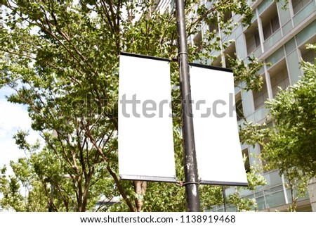 The blank advertising banner suspended on the street lamp pole with the tree and building facade background. #1138919468