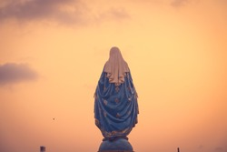 The blessed Virgin Mary statue figure in a warm tone - sunset scene. Catholic praying for our lady - The Virgin Mary.