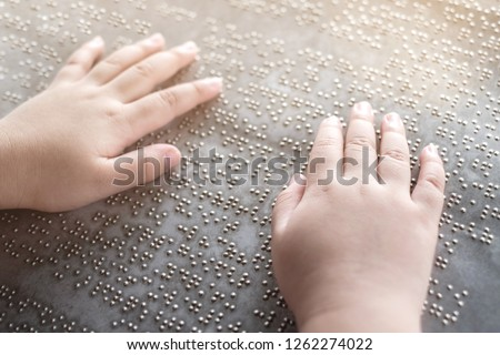 The blind kid's hand and fingers touching the Braille letters on the metal plate #1262274022