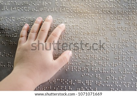 The blind kid's hand and fingers touching the Braille letters on the metal plate to understand an information #1071071669