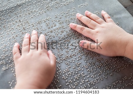 The blind kid's hand and fingers touching the Braille letters on the metal plate to understand an information #1194604183