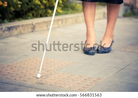 The blind woman is walking on the sidewalk, using a cane. #566831563