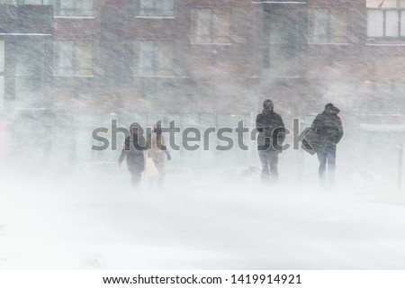 The blizzard, strong wind, sleet, against the background of houses blurred silhouettes of people, they try to hide from bad weather, overcome all difficulties of severe climate. go to the bus stop.