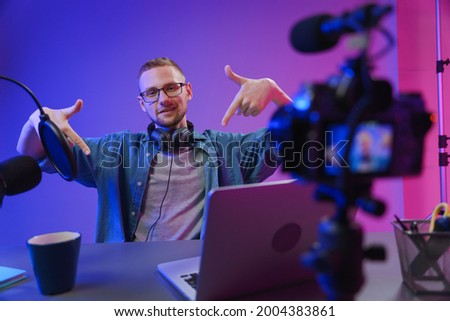 The blogger points his fingers down so that viewers will pay attention to the pop-up 'subscribe'icon. A vlogger needs to attract as many followers as possible to his channel. Photo stock ©