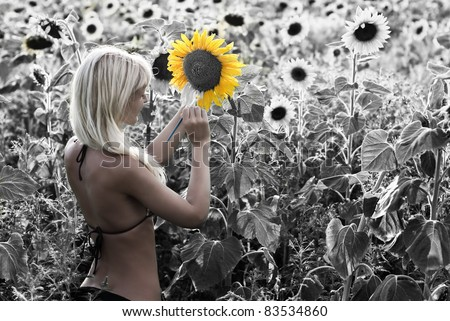 The blond girl painting the sunflower field in the bright colors - the concept of transformation of life - all in your hands