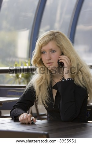 The blond young girl speaking by phone