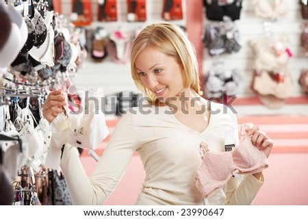 The blonde chooses a brassiere in shop