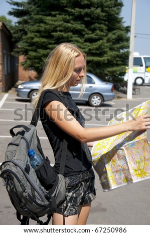 The blonde girl-traveler with a map of the city and a backpack in the street.
