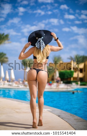 Stock Photo the blonde girl with a beautiful figure goes to the pool area in a black hat and bathing suit. Back view