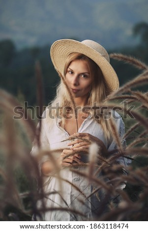 The blonde in a linen dress walks among herbs and wildflowers on a meadow in the mountains. A woman in the Boho style, resting in the countryside, a simple village lifestyle Сток-фото ©