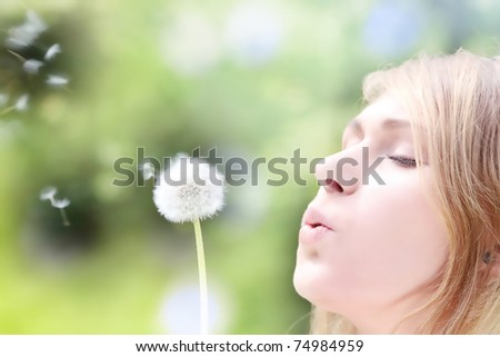 The blonde sits in park on a grass with a dandelion in hands and blowing