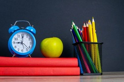 The blue alarm clock along with multi-colored pencils stand on a stack of red books, next to an apple.