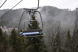 The blue bench of the old ski lift and the woods below