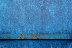 The blue metal fence is covered with ice water. Ice glistens in the sun on blue metal. Reflections of the sun on the surface of a blue icy surface. .Blue paint metal plate texture and background.