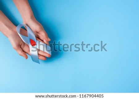 the blue ribbon awareness with red blood drop in woman hands isolated on a blue background. World diabetes day,14 november. Copy space. Top view