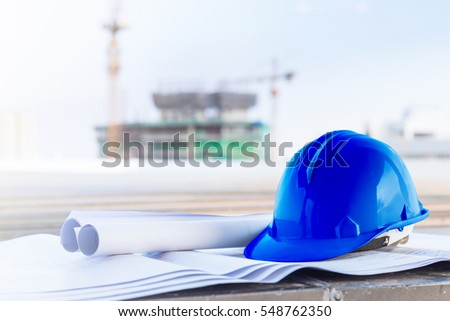 The blue safety helmet and the blueprint at construction site with crane background