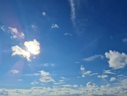 The Blue sky clouds and sun. Sky and sun background.