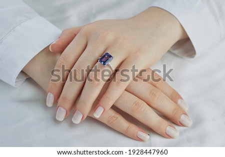 The blue stone diamond ring is on a lady finger. A very expensive custom ring. Photo stock ©