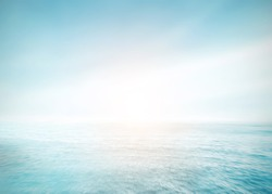 The blur cool sea background on horizon tropical sandy beach; relaxing outdoors vacation with heavenly mind view at a resort deck touching sunshine, sky surf summer clouds and light blue wave ocean.