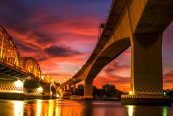 The blurred background of the twilight evening by the river, the natural color changes, the bridge over the river (Bangkok Bridge) is one of the major transportation bridges in Bangkok, Thailand
