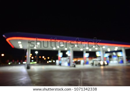 The blurred image of a car being fueled at a gas station. Absract blur petrol gas station in night background with light bokeh