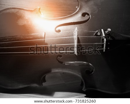 The blurry light design background of violin,string instrument put on wood board ,front side body,vintage tone,grainy film style,abstract art design. #731825260