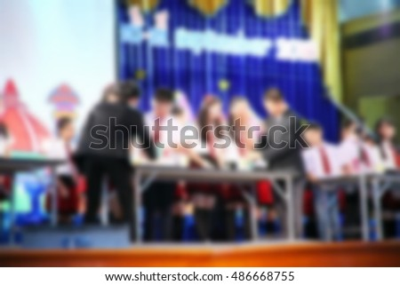 The blurry photo of young student do activity on stage of meeting hall scene represent the people and activity concept related background idea.