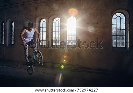 The BMX rider jumps with a bicycle in a dark hall in sunray. #732974227