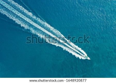 The boat is moving at high speed on the sea. A long Wake follows the boat. Blurred movement. Shooting from a drone.