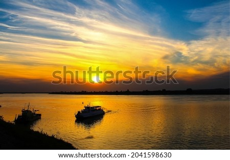 The boat sails on the river at dawn. River boat at dawn. Sunrise over river. Early morning on river dawn