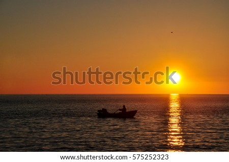 The boat with the fishermen in the sea at sunset.