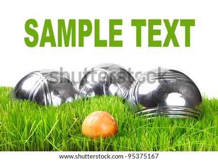 The bocce balls on a green grass. Picture with space for your text.