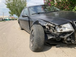 The body of the car is damaged as a result of an accident. High speed head on a car traffic accident. Dents on the car body after a collision on the highway