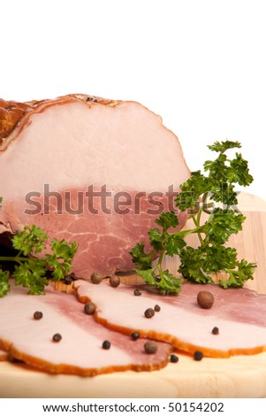 The boiled pork decorated by pepper and a parsley on a white background