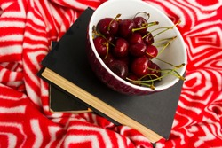 The book and red ripe cherries. Two ripe cherries look out of the book. Cherries as an unusual bookmark for the book. Notebook for Recipes and Cherries.the concept of summer vacation and relax